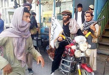 Një luftëtar taleban ulur në motorin e tij të stolisur me një flamur të talebanëve në një rrugë në Kunduz, Afganistan.