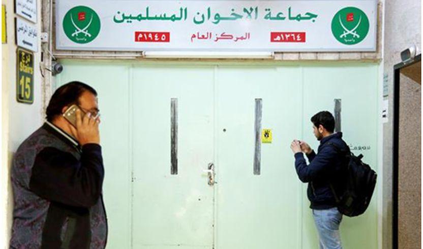 Një burrë fotografon hyrjen kryesore të zyrës së selisë të ' Vëllazërisë Myslimane' , vulosjen me dyll të zyrës, pasi ishte bastisur dhe mbyllur nga policia, në Aman, Jordan, të mërkurën.